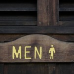 Engraved wooden men's bathroom sign.